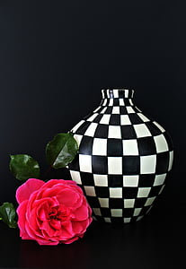 red rose near white and black checked ceramic vase