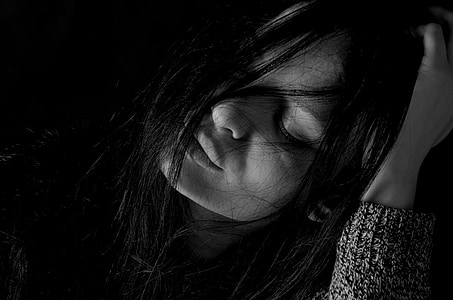 grayscale photography of woman holding her head