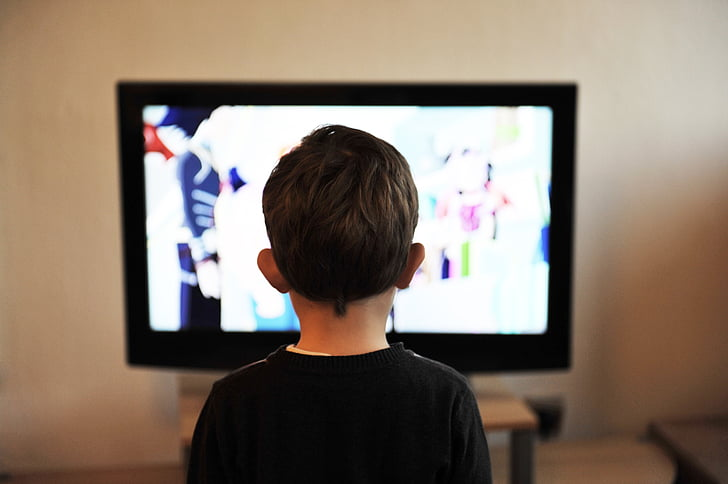 Royalty-Free photo: Boy standing in front TV turned on | PickPik