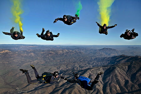 seven persons sky diving with parachutes under clear blue sky