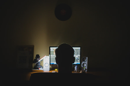 man playing online games on computer