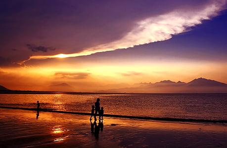 silhouette photo of four person near seashore