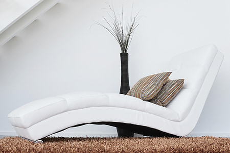 white leather lounger sofa on top of brown area rug
