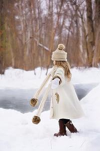 girl playing outside with snow in forest