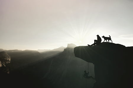 man and dog on top of mountain