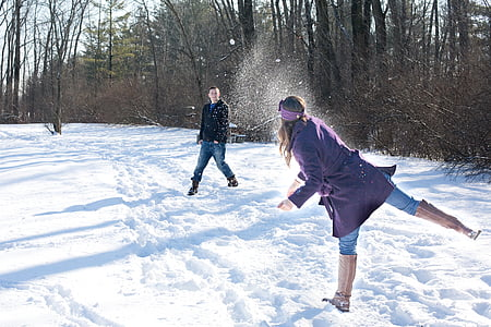 man and woman playing outside during winter