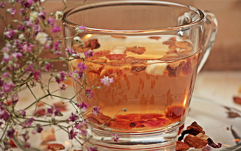 clear glass teacup filled with orange liquid in closeup photo