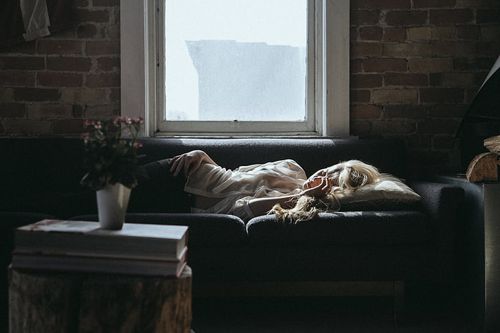 woman in white shirt sleeping on black couch near glass window with white frame during daytime