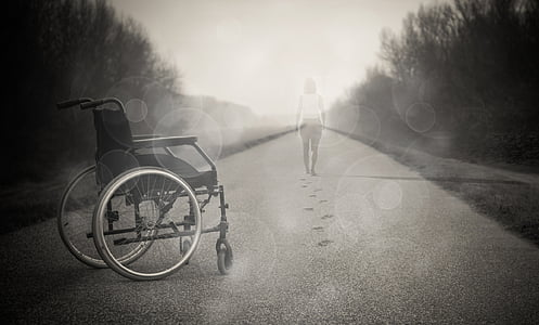 grayscale photo of wheelchair and faded woman