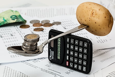 brown potato and round silver-and-gold-colored coins stack balancing on gray steel spoon and black digital calculator