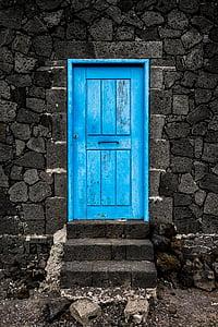 blue wooden door on gray concrete structure