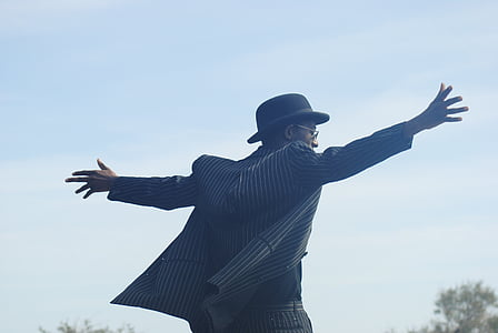 person wearing arms sideward facing field