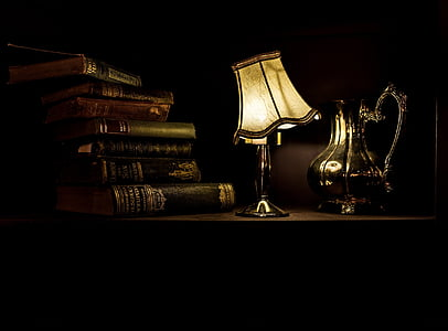 photo of white table lamp near books