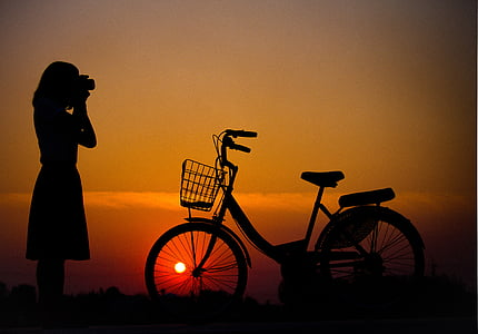 silhouette of woman and bicycle on