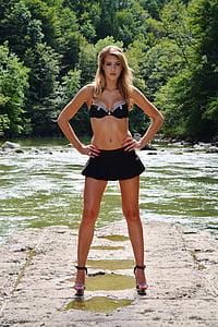 standing woman wearing black bra and black mini skirt
