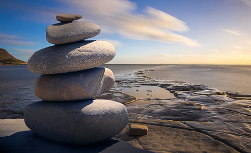 stack of grey rocks near brown surface under blue sky