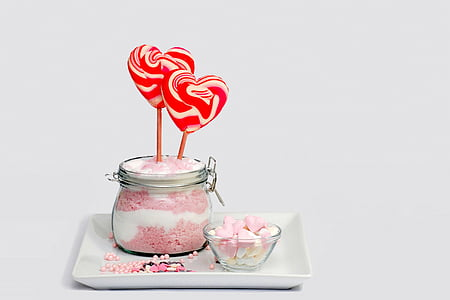 two heart-shaped red and white candies and clear glass jar