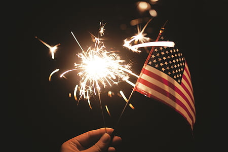 person holding USA flag and fire cracker