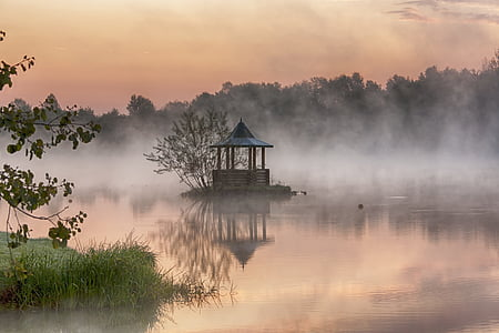 brown gazebo on body of water surrounded of trees during golden hour