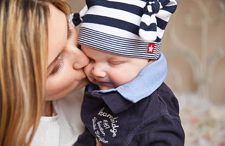woman kissing baby on cheek