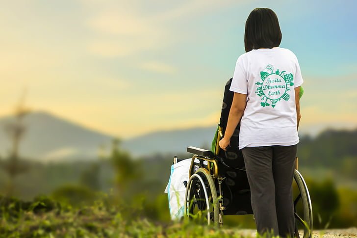 woman in white t-shirt holding black self-propelled wheelchair