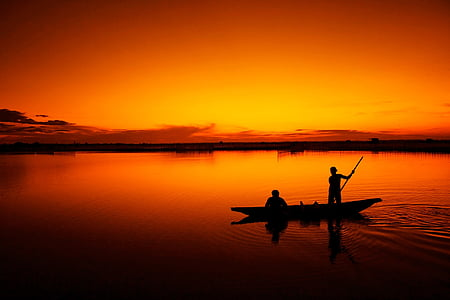 silhouette of two men on canoe during sunset