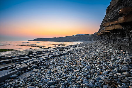 photography of stones near body of water