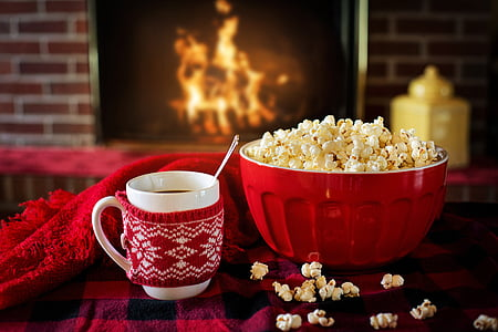 red bowl of popcorn beside coffee mug