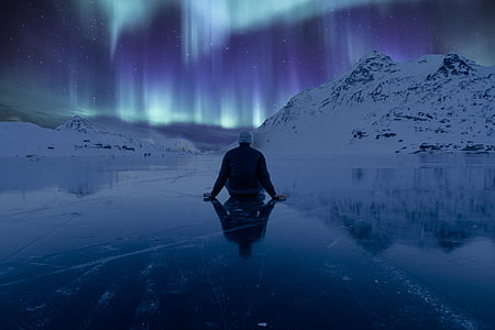 person sitting on ice surface watching aurora lights