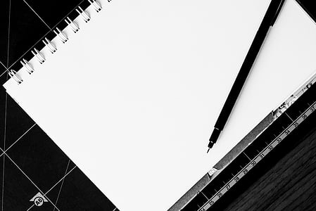 white notebook and black ballpoint pen