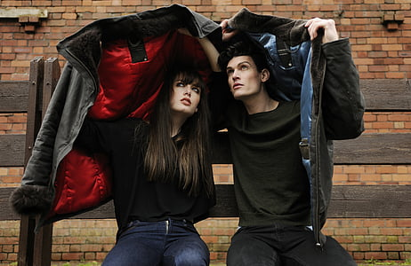 man and woman holding jackets sits near brown brick wall during daytime