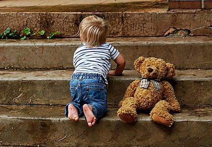 toddler beside brown bear plush toy climbing flight of stairs