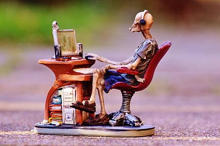 skeleton sitting in front of desk ceramic figurine