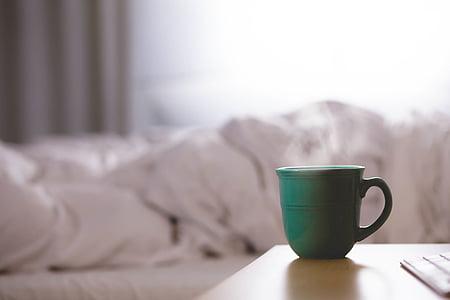 green teacup near white bed sheet
