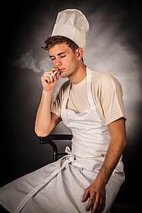 man in white apron smoking cigarette