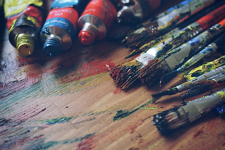 assorted-color paintbrush and paint on brown wooden parquet