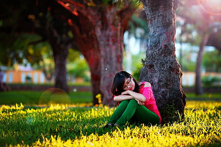 woman in pink cold-shoulder and green pants sitting on grass under brown tree during daytime