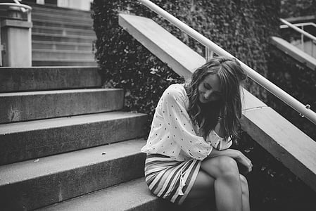 grayscale photo of woman sitting on stairs