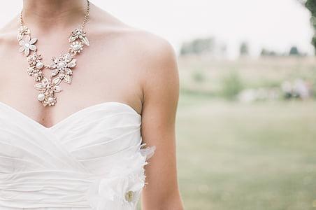 woman wears white sweetheart wedding dress on open field during daytime
