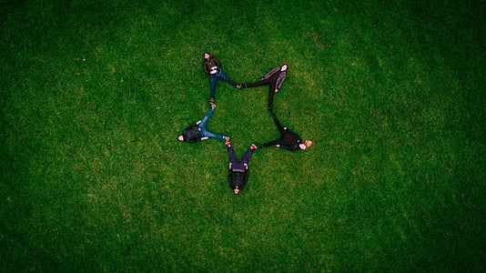 five people forming a star while lying on grass field