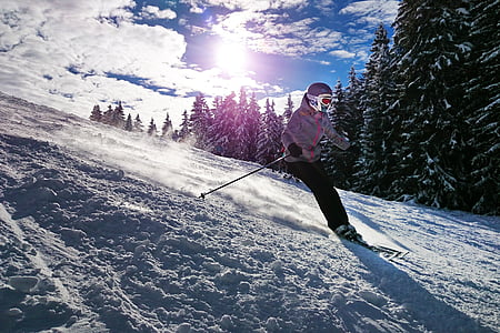 person in gray winter jacket and black pants doing ski during daytime