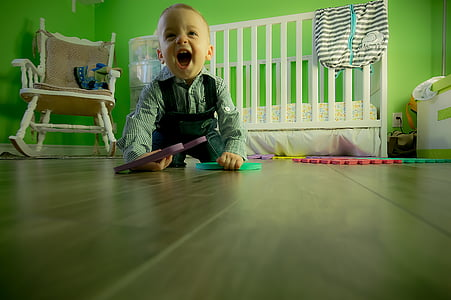 boy wearing long-sleeve shirt crawling near crib