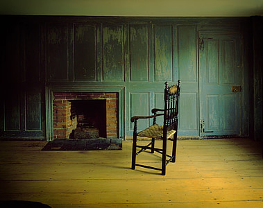 black wooden armchair near brown and black brick fireplace