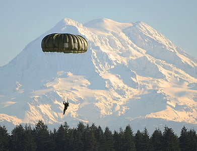 man using green parachute during daytime and mountain alps at distance