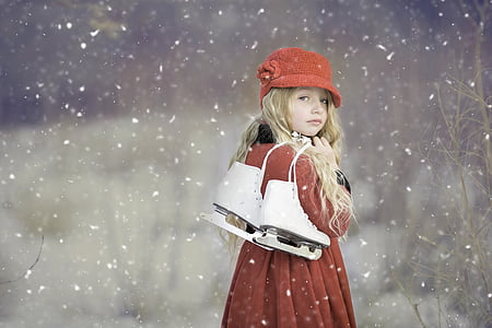woman wearing red coat holding figure skate while raining snow