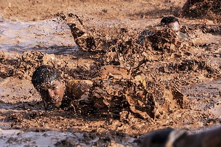 men crawling on mud during daytime