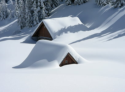 two brown huts covered in snow