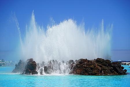 splash of water on brown islet during daytime