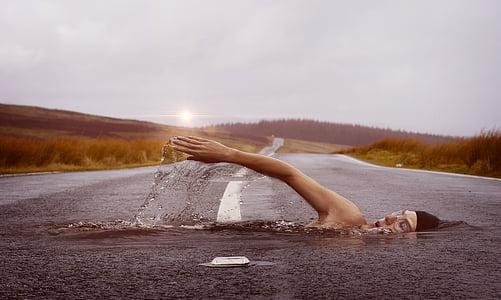 edited photo of man swimming on asphalt road