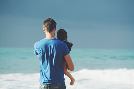 man carrying baby near sea